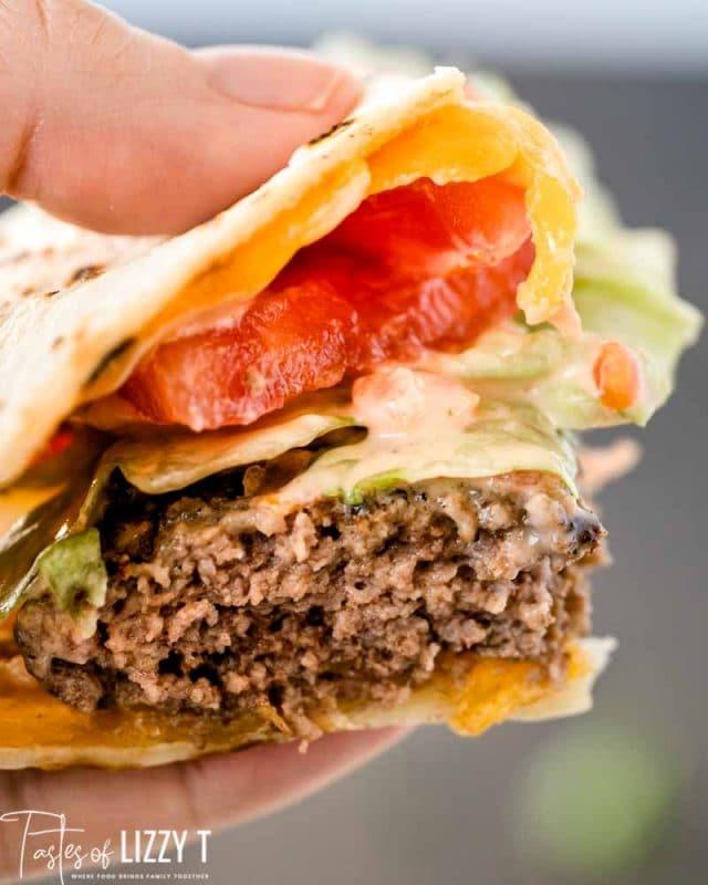 hand holding bite of quesadilla burger