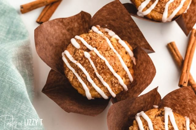 overhead view of a glazed cinnamon coffee cake muffin in a brown wrapper