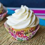 white cupcake with white frosting in flowered cupcake liner