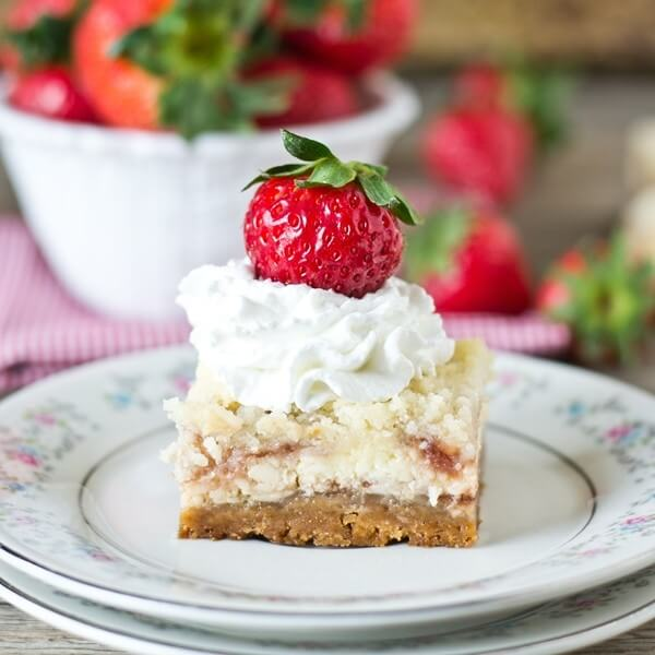 Strawberry Shortcake Cheesecake Bars on a plate with whipped cream and strawberry
