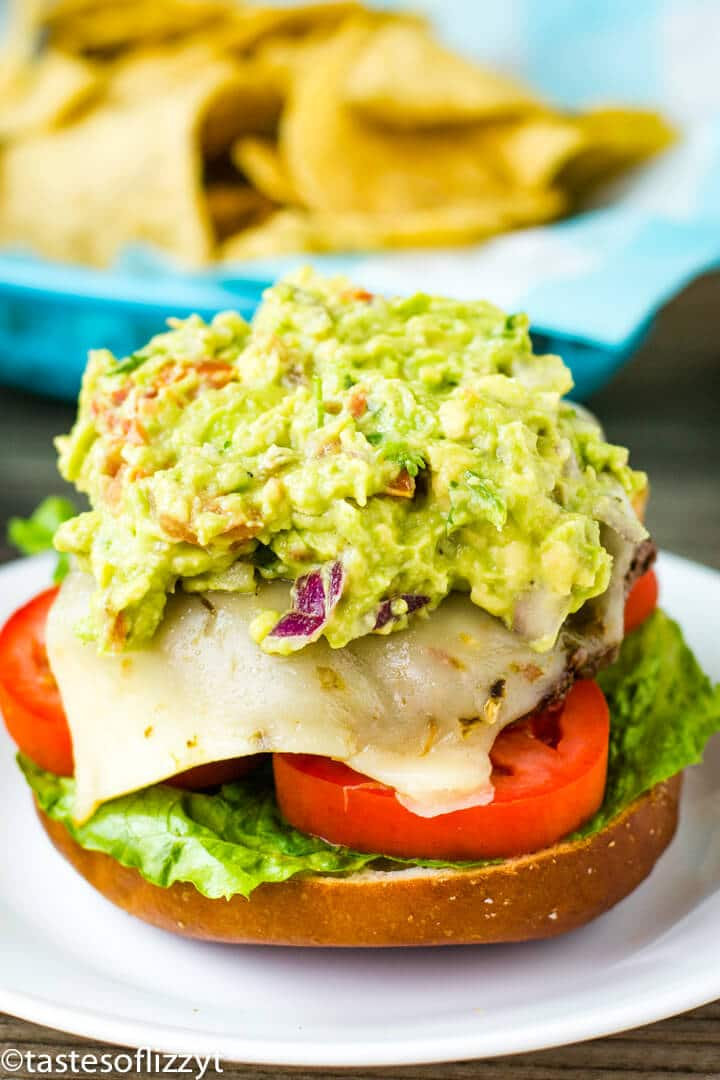 A close up of a burger on a plate, with Guacamole