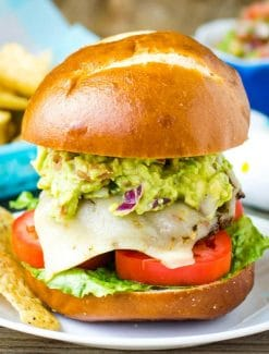 A sandwich with lettuce and fries on a plate, with Guacamole
