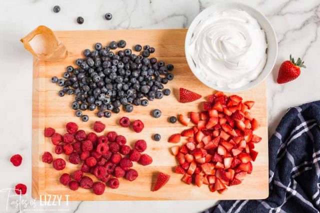 blueberries, raspberries and strawberries on a cutting board