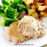 fork tender pork chop on a plate with potatoes and broccoli
