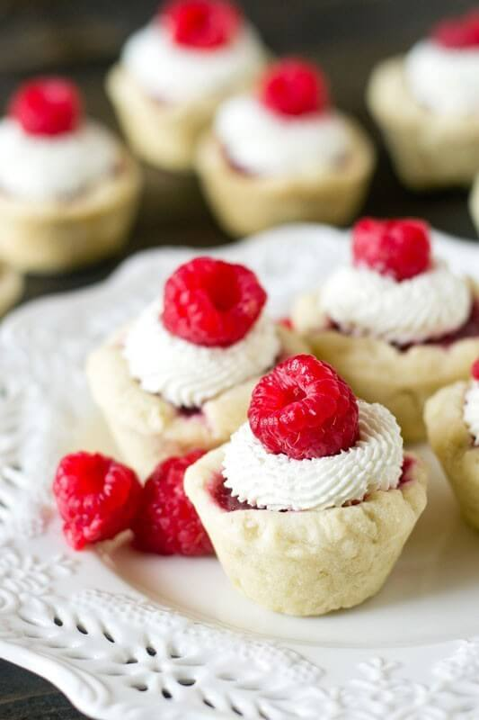 Raspberry Tart with Mascarpone Cream. Bite-size sweet treats with a homemade raspberry pie filling and light cream on top.