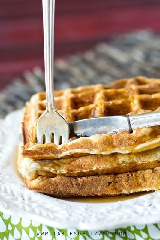 fork and knife cutting in to a stack of homemade apple waffles