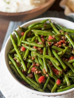 Christmas green beans are dressed up with pimentos and chopped pecans that are caramelized in butter and honey. A simple side dish to complete your dinner. Christmas Green Beans with Toasted Pecans #christmas #vegetables #recipe