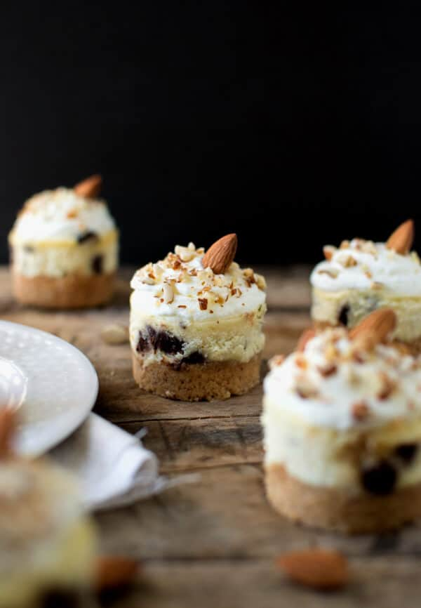 Almond Chocolate Chip Mini Cheesecakes with a buttery almond crust and topped with almond whipped cream. First, a buttery almond crust with a hint of sweetness. Then a rich chocolate chip cheesecake, lastly topped with a bit of almond whipped cream and more toasted almonds.