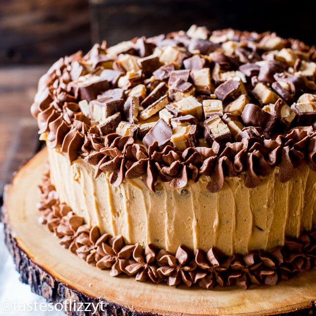 Chocolate cake layered with peanut butter frosting and chopped peanut butter Snickers bars make this Snickers cake a must for all chocolate peanut butter lovers.
