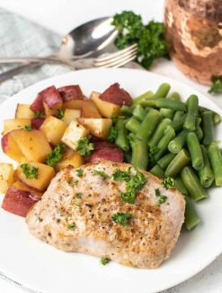 pork chop, potatoes and green beans on a plate