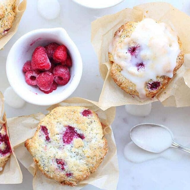 two lemon poppyseed raspberry muffins with a bowl of raspberries