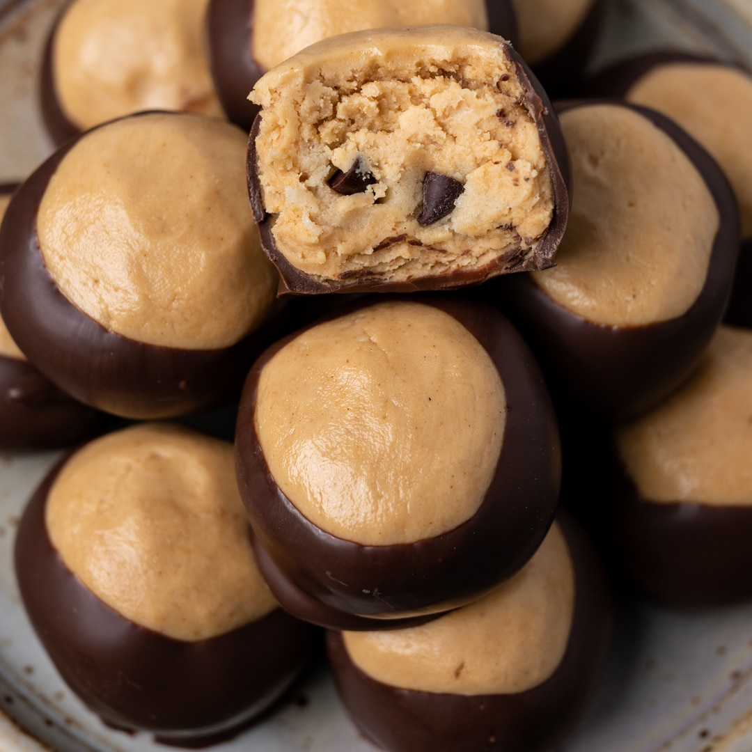 cookie dough buckeyes on a plate with one bite out