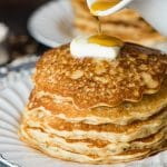 stack of oatmeal pancakes with butter and syrup