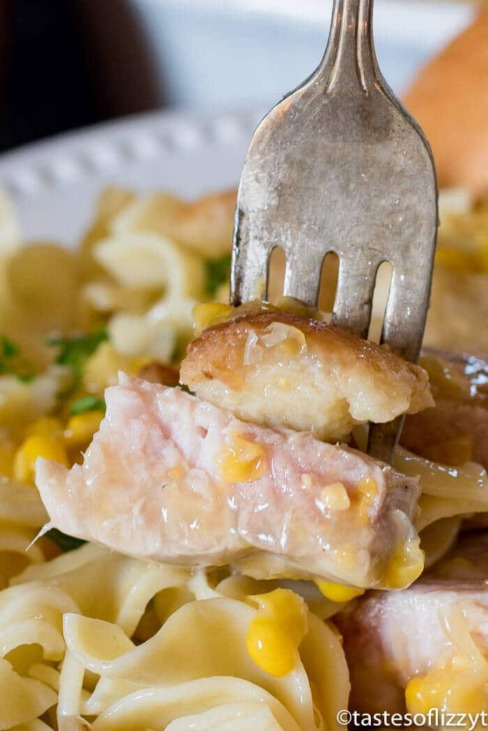 fork holding bites of pork chops casserole with creamed corn