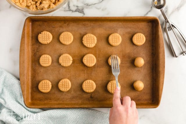 pressing fork onto peanut butter cookies