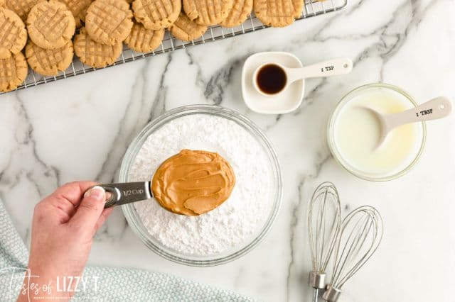 peanut butter in a measuring cup over powdered sugar