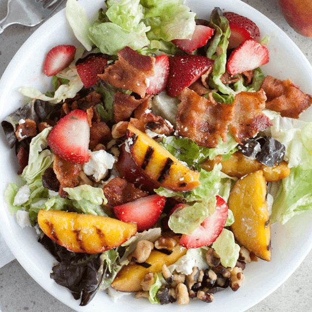 overhead shot of dinner salad with grilled peaches, strawberries and bacon