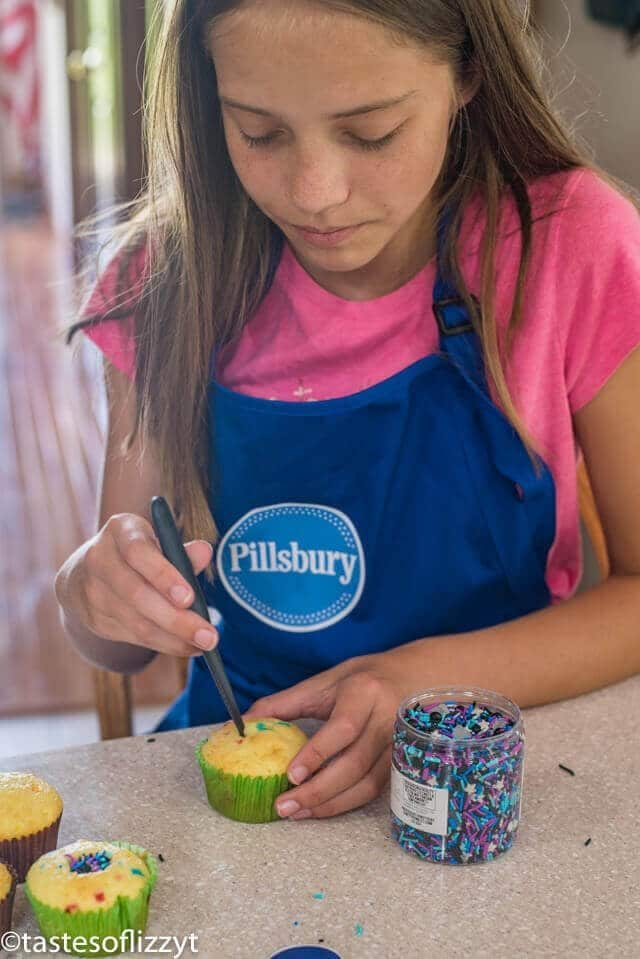 A woman sitting at a table making cupcakes
