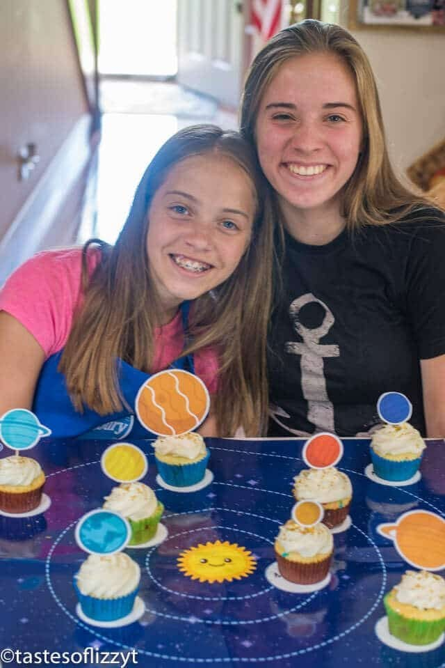 sisters with solar system cupcakes