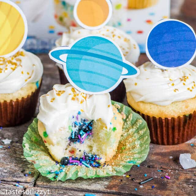 solar system cupcakes, one with a bite out