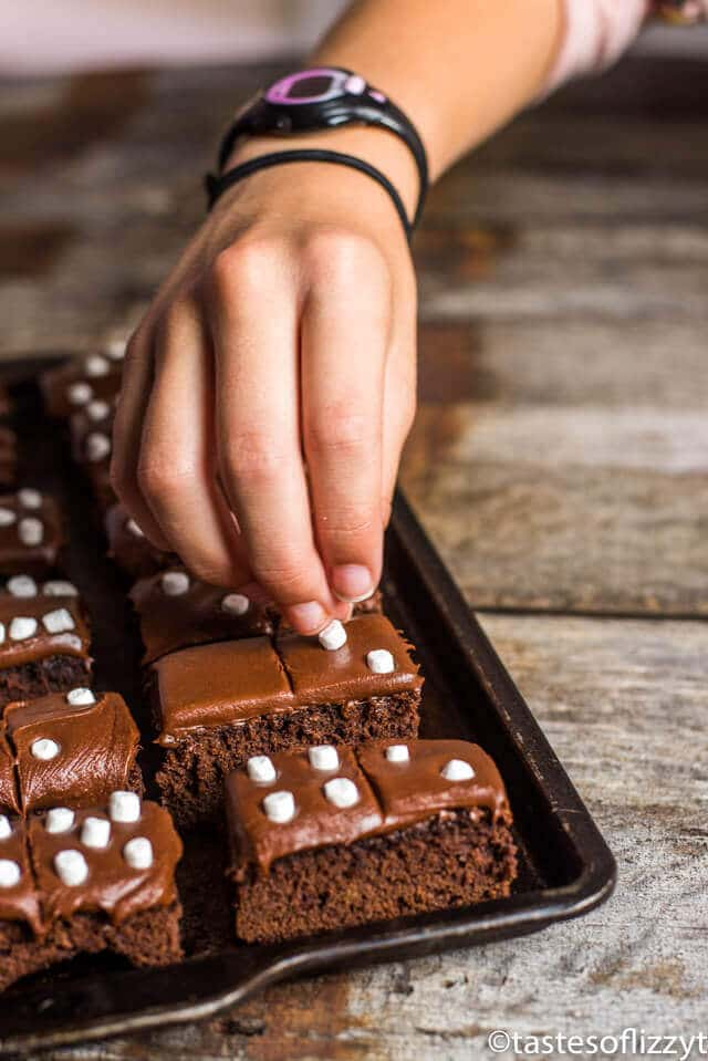 hand placing marshmallows on domino brownies
