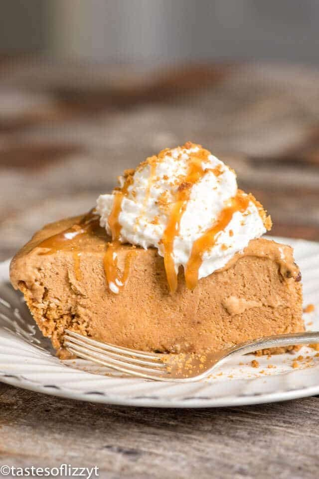 a slice of frozen dessert pumpkin pie topped with whipped cream and caramel sauce