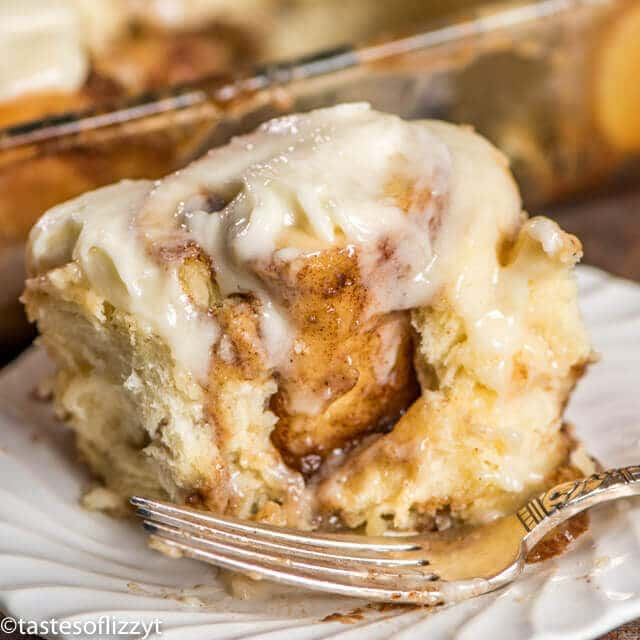 cinnamon roll on a plate with a bite out of it