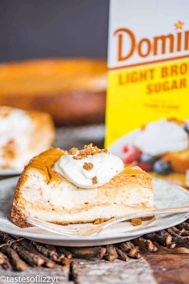 swirled pumpkin cheesecake topped with whipped cream and gingersnap cookie crumbs