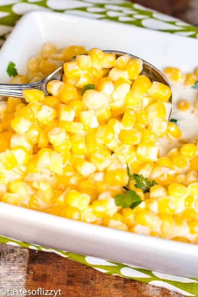 bowl of crock pot creamed corn with a spoon