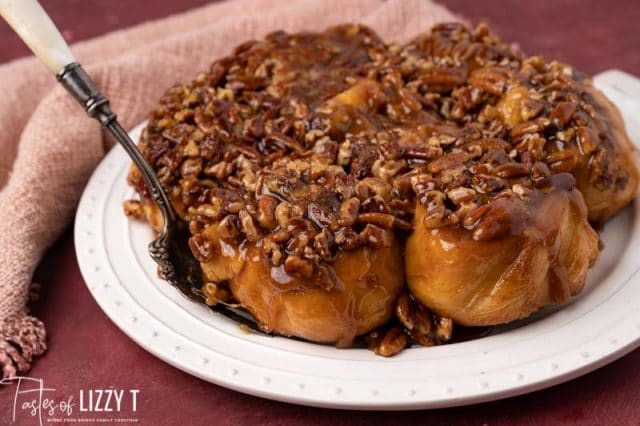 plate of caramel pecan sticky buns with a serving spoon