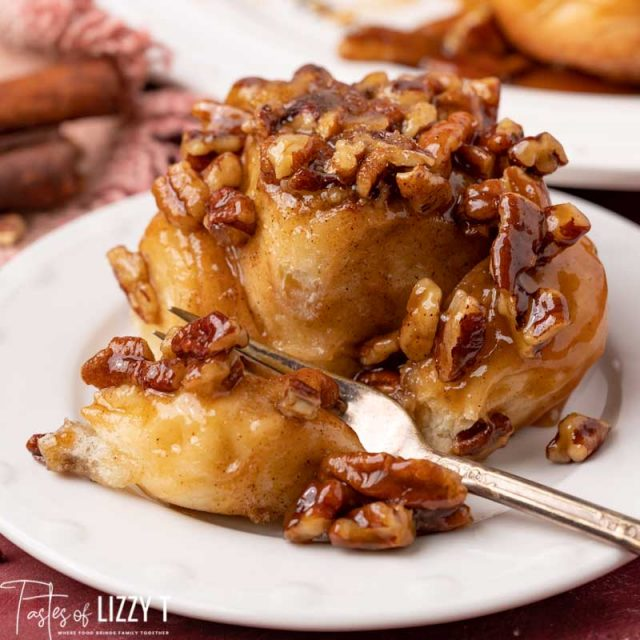 pecan sticky bun on a plate with a bite on a fork