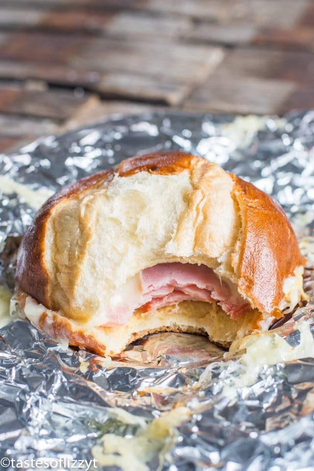 A half eaten sandwich sitting on top of foil
