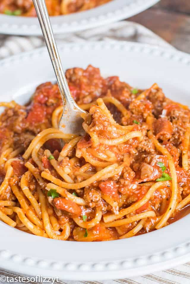 spaghetti with meat sauce on a plate with a fork