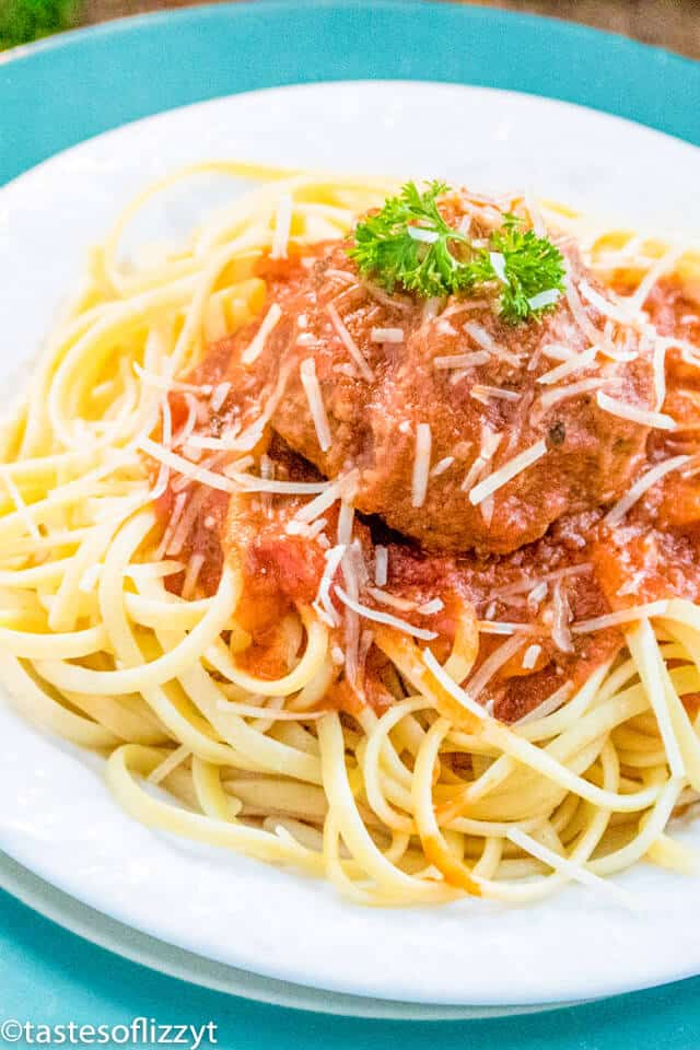 A plate of pasta with sauce and meatballs