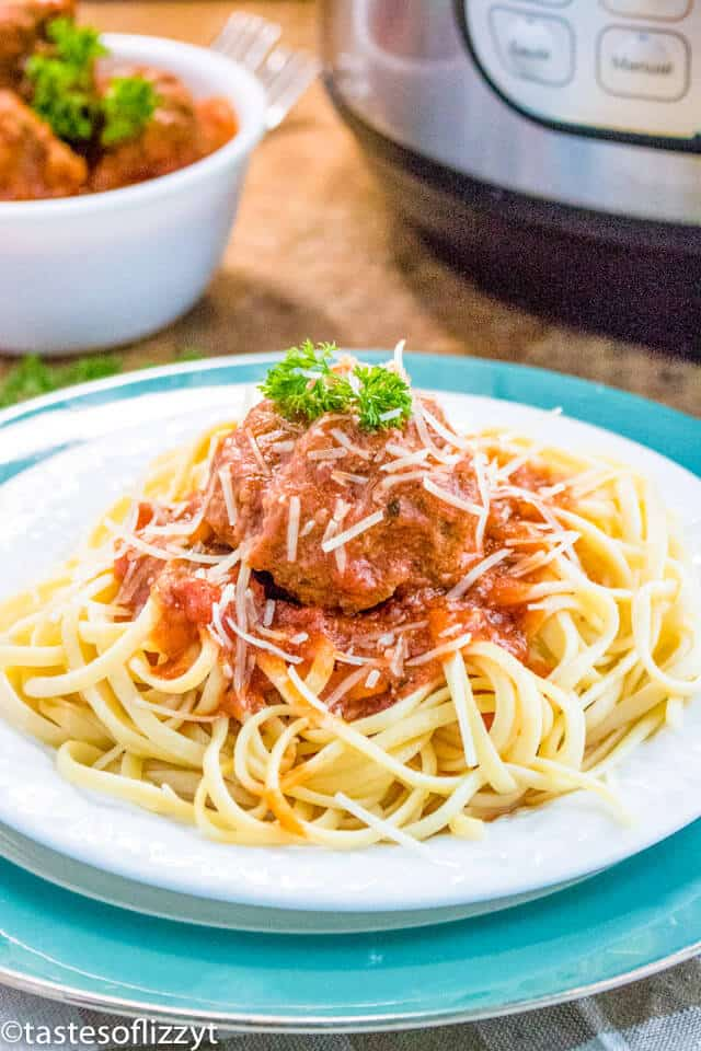 A bowl of pasta sits on a plate, with Meatball and Sauce