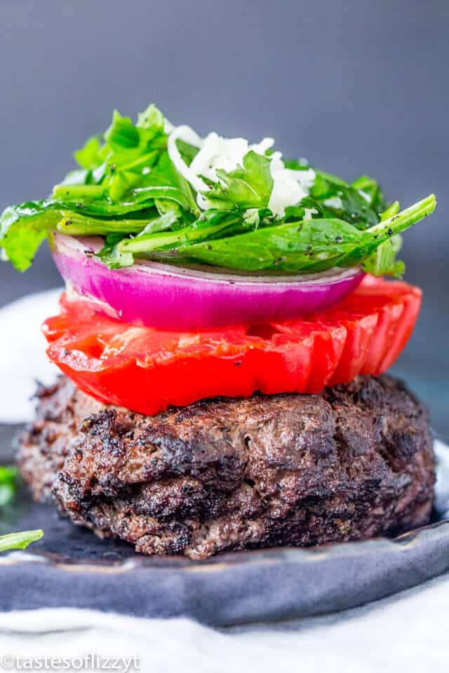 A close up of a burger with veggies