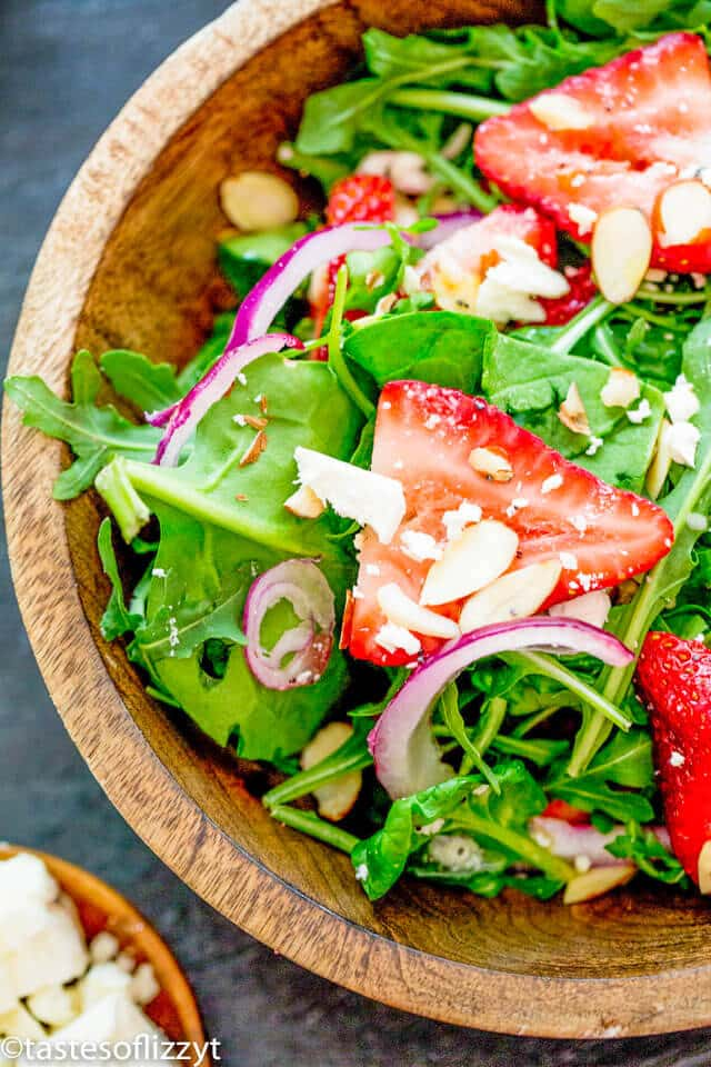 A bowl of salad on a plate, with Strawberry and Spinach