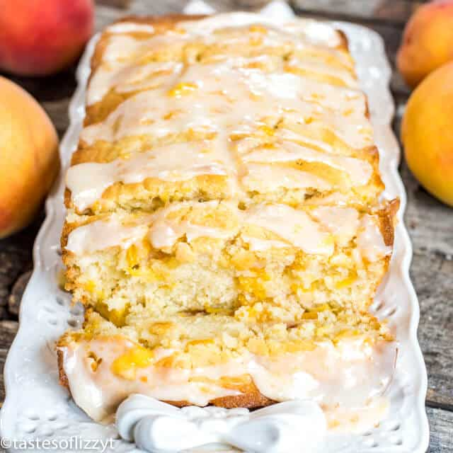 peach bread with glaze sliced on a white platter