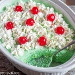green jello salad with whipped cream and cherries