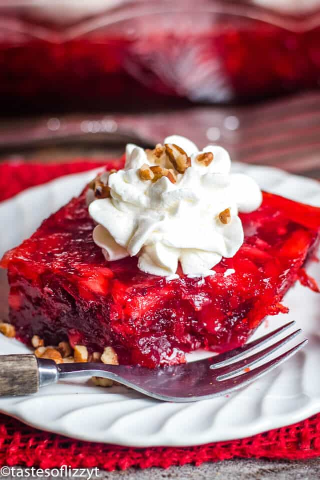 piece of cranberry jello with whipped cream and pecans