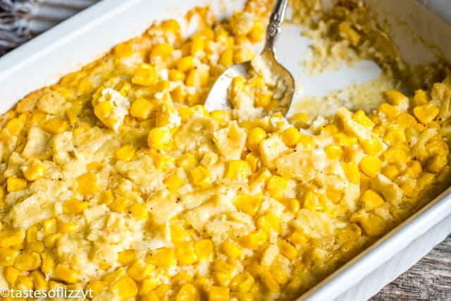 baked scalloped corn in a dish with a spoon