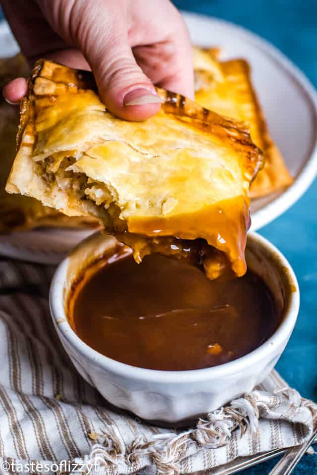 hand dipping sausage hand pies in gravy