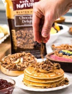 A plate of food that is on a cutting board with a pancake, with Granola