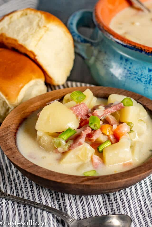 Ham and Potato Soup in wood bowl with rolls