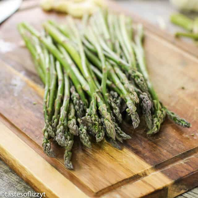 A wooden cutting board with asparagus