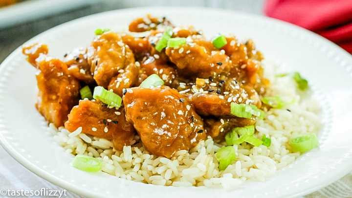 A plate of food with rice meat and vegetables, with General Tso\'s chicken
