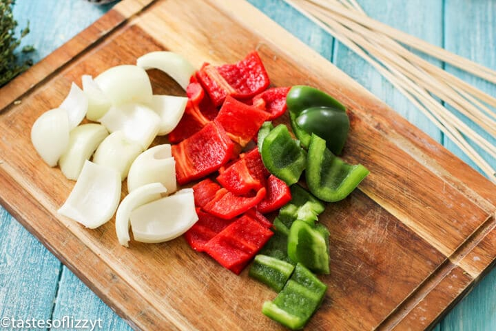 peppers and onions on a wooden cutting board