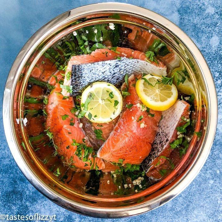 salmon marinating in a bowl with lemons