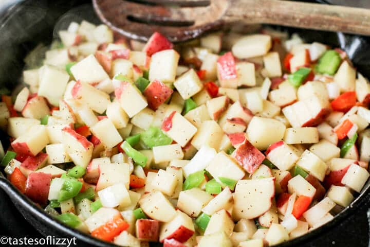 A pan filled with potatoes, peppers and onions