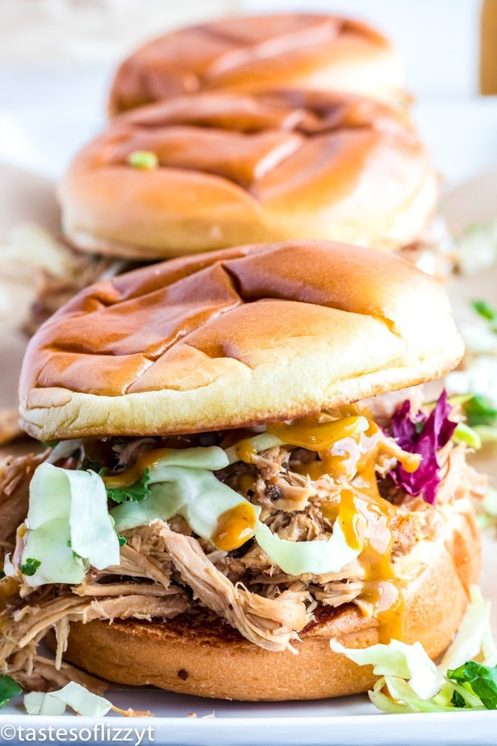 A close up of a sandwich on a plate, with Pulled pork